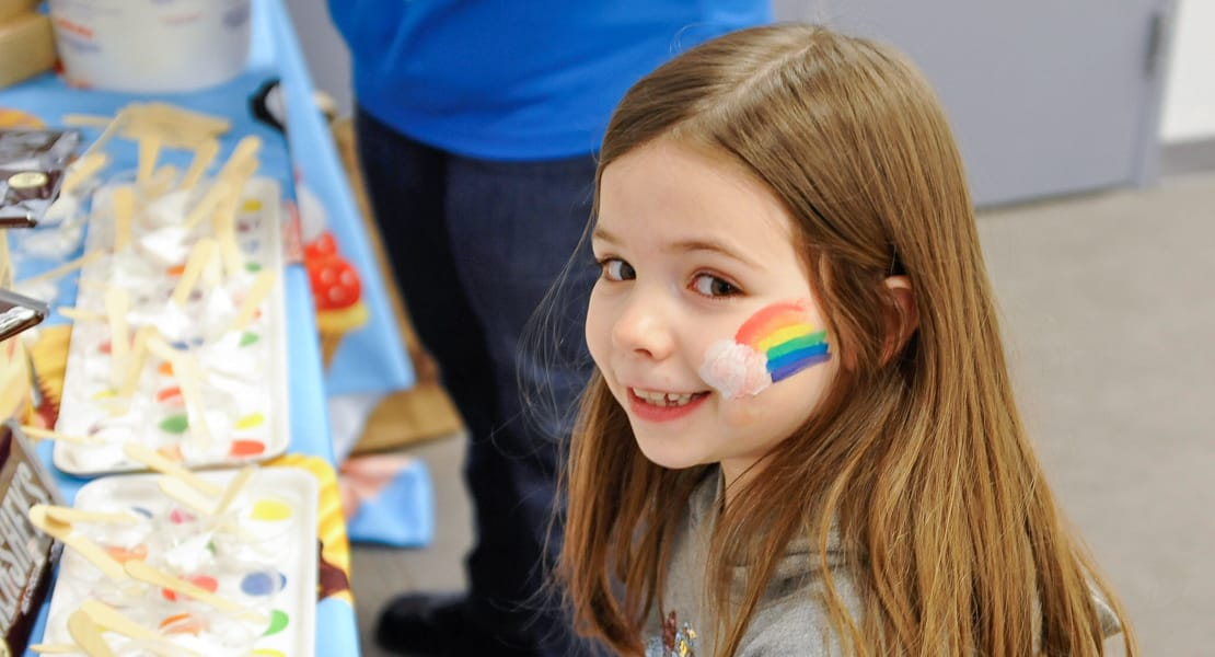 Girl with rainbow face paint on cheek at arts and crafts